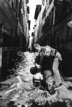 Un uomo salvataggio un ragazzo su una strada allagata di Firenze