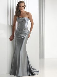 Sheath, fit and flare silver dress with a strapless neckline featuring ruching  and  asymmetrical beading that sparkles on the bodice with a corset  back.