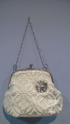 Bolso en tela adamascada color hielo y plata y cierre metálico de boquilla con cadena corta.Broche de quita y pon.