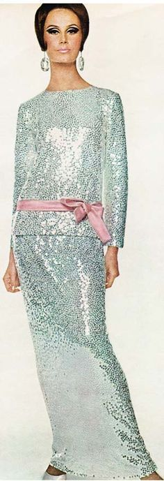 A strip of pink satin tied at the hips offsets the silver sequined tunic and…