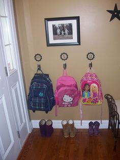 Backpack Organization Wall -- I like the initials.  Uses command hooks?  Nice to try before you start drilling and nailing.