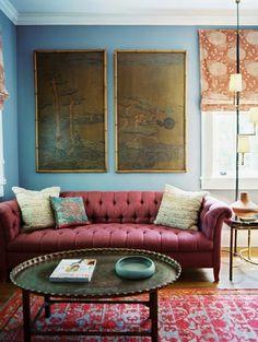 Bank in kleur marsala tegen blauwe muur | ELLE Decoration NL
