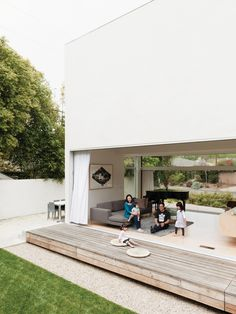 The Lai family—Mayuko, baby Shota on her lap, David, Maya, and Yumi sitting on a cushion on the deck—relaxes in their indoor-outdoor living space, made by opening the glass sliding doors to connect the living room and engawa deck.  Photo by: Jessica Haye and Clark Hsiao