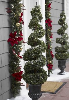 Create a cohesive, classic Christmas look with beautiful garland and prelit decorative trees outside your home.