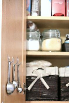 Perfect Pantry Organization. Use command hooks to hang measuring spoons and cups inside a cabinet