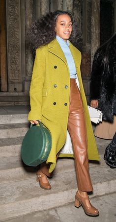 Solange Knowles wears a statement green coat with a blue sweater, tan leather pants, a top handle Manseur Gavriel bag and tan Mary Jane shoes