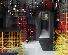 Wine bottles are displayed in rainbow-coloured cages in this wine shop in Stuttgart, Germany, by local studio Furch Gestaltung + Produktion