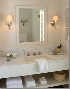 Sink with a honed marble countertop and open shelving below. The vanity is so classic looking, simple yet elegant.