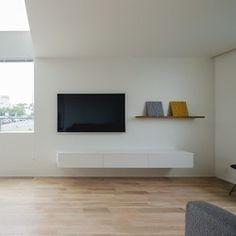 1階リビング。吹抜けに面する窓の下端に合わせてテレビを壁掛けで設置。シンプルな幅2.1mのTVボードを造作し、壁固定で床から浮かせて仕上げた。 | 八日市の家