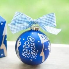 """Go team, go! Kick off the season with the cheer-raising University of Kentucky Crowd Cheer Ornament! Designed with FAN-tastic """"Go Big Blue!"""" writing and cheering FAN-atics, it's a high-scoring way to celebrate gameday, holiday or everyday. All collegiate ornaments come boxed and tied with a coordinating ribbon making them the perfect gift for anyone."""