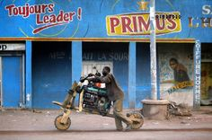 A man in Goma, Democratic Republic of Congo, transports a diesel generator on his chikudu, a primitive wooden bicycle capable of carrying heavy loads. (Jerome Delay, Associated Press / August 2, 2012)