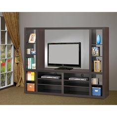 The Wildon Home Entertainment Center is a simple yet stylish wall unit, which is sure to light up your living room. Having a contemporary design, this chic piece of furniture is high on utility too. Occupying very less space in the room, it fits all your entertainment gizmos at one place. The deep tones of brown make the unit look elegant and sophisticated. Its smooth cappuccino finish seamlessly complements with most type of interiors.  Offering a huge central cavity, the entertainment…
