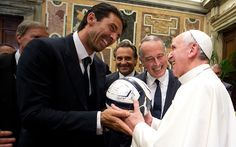 Pope Francis receives an autographed ball from Italy goalkeeper Gianluigi Buffon, left, as coach Cesare Prandelli, centre, and president of the Italian soccer federation Giancarlo Abete smile, during a private audience at the Vatican