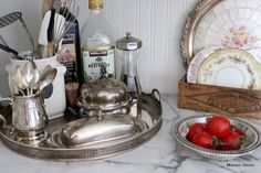 Silver tray with silver butter dish, another domed silver  butter holds garlic bulbs and a picure for spoons.