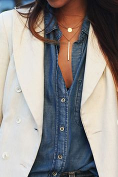 Chambray shirt paired with a white blazer and gold layered necklaces.