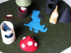 Child activity mat - Green mossy forest floor. Hand sewn felt gnomes stuffed with off-white wool roving. 3 felt gnome homes: mushroom, cave & tree, roofs are removable. The white spots on the red mushroom roof are needle felted using off-white wool roving. Green mossy forest floor is a wool sweater that was wet felted.