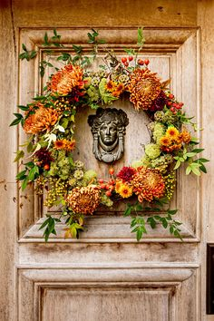 Use fresh or faux chrysanthemum stems to add classic fall character to your fall wreath. Spider, button, and garden mums were pulled together with hypericum berries, nandina foliage, and lotus pods to create this fiery door greeter. #falldecor #fallideas #wreathideas #fallwreath #wreath #bhg