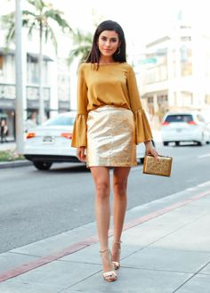 """Go bold and super festive for a dinner party, playing with fabrics and shapes that wouldn't fly for the office. """"When I think of the holidays, the color gold instantly comes to mind. This look would be great for an intimate dinner party."""" - blogger Sazan Hendrix  Rochas blouse, $975, matchesfashion.com; Edie Parker clutch, $1,295, neimanmarcus.com; Tory Burch sandals, $295, nordstrom.com; Anine Bing skirt, $499, aninebing.com"""
