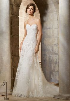 """Wedding Gowns By Blu featuring Elegant Alencon Lace Appliques on Soft Net Gown with Scalloped Hemline Lace Exquisite patterns of Alencon lace adorn the decadent bodice of this A-line wedding dress, complete with a full Net over-skirt, edged in lace. Accented with a stunning sweetheart neckline, and finished with covered button detail along the back. Available in Three Lengths: 55"""", 58"""", 61"""" . Colors Available: White, Ivory"""
