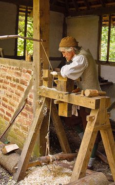 Tom the wood turner uses a pole lathe to fashion a wooden spoon in Little Woodham Living History Village by Anguskirk