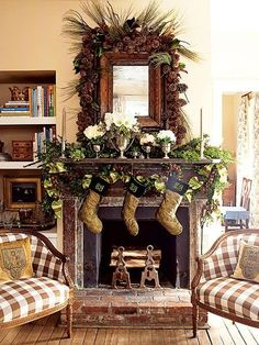 35 Beautiful Christmas Mantels - Christmas Decorating -A pair of 10th-century Danish chairs flank the living room's fireplace and mantel, which is decorated with sprays of boxwood, plenty of pine cones, and flowers in all-white to match the brown-and-green Christmas stockings. The effect is charming and casual.