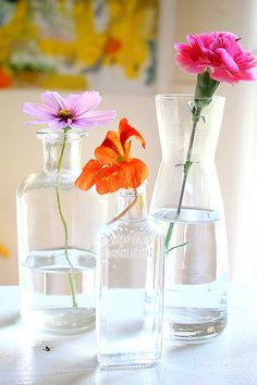 so simple yet so pretty- jars of single stem flowers. i'd use different flowers, but love this idea.