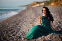 Красивая девушка в зеленом платье сидит на пляже и смотрит вдаль