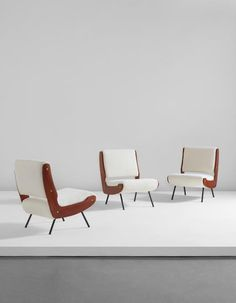 GIANFRANCO FRATTINI  Set of three lounge chairs  circa 1955  Walnut, painted steel, fabric, brass.  Each: 30 3/4 x 22 1/2 x 30 1/2 in. (78.1 x 57.2 x 77.5 cm)  Manufactured by Cassina, Meda, Italy.