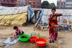 By James Nachtwey A woman and children at a squalid  tent encampment in central Kathmandu, Nepal, nearly a year after the devastating 2015 earthquakes, March 31, 2016.