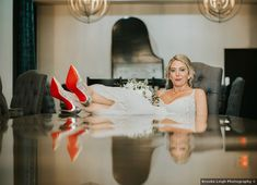 Bridal photography sitting in office chair resting red-bottomed shoes on the table