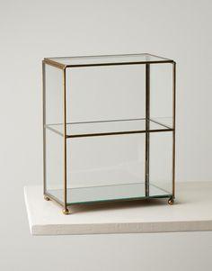 Elegant litet skåp i glas för dina smycken eller parfymflaskor. Skåpets alla sidor samt hyllplan är helt i glas och fogarna i mässing. Skåpet har en spegel i botten som ger en härlig extra effekt till det du väljer att ställa in.