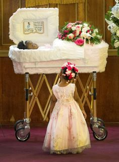 The body of Londyn Samuels, 1, lies in a casket as her sister, Paris, 3, looks up at her during the funeral at New Hope Baptist Church in New Orleans on Saturday, September 7, 2013. Samuels was murdered while in the arms of her babysitter.