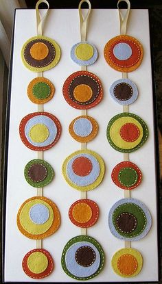 """Mod Circles - Felt wall hanging Trio    Finished custom order.  Made with wool-blend felt, handstitched together on grosgrain ribbon.  Light Brown, Copper, Pumpkin Spice, Copper, Moss, Robin's Egg Blue, Mellow Yellow.  Each wall hanging measures 21"""" (53.3cm) long, and 3"""" (8cm) at its widest."""