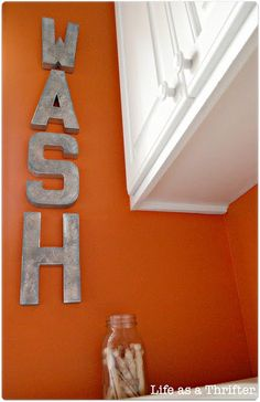 create some word art as décor for laundry room.  It only required spray painting some craft store cardboard letters and then lightly sanding to remove the sheen and give them the look of metal. This method is so simple and can be customized to fit any room in the house.