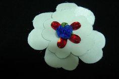 flor blanca compuesta con rosita azulón y abalorios de cristal rojo