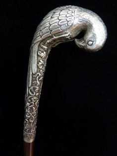 Silver parrot cane from Oomersi Mawji. (India, circa 1880). A mahogany cane with very fine silver handle of a parrot. The handle is tamped O.M. For Oomersi Mawji, the noted Gujarat silver smith who was royal silver smith to the Maharaos of Kutch.