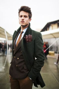 Shop this look for $1,204:  http://lookastic.com/men/looks/overcoat-and-double-breasted-blazer-and-gloves-and-tie-and-dress-shirt-and-chinos/1117  — Green Overcoat  — Brown Double Breasted Blazer  — Brown Leather Gloves  — Tobacco Knit Tie  — White Dress Shirt  — Tobacco Chinos