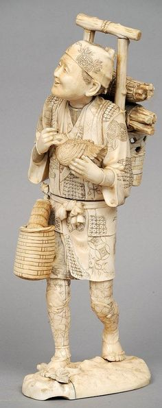 A large 19th century Japanese ivory okimono Formed as a woodsman, modelled carrying bundles of wood on his back and holding a bird. 35 cms high.