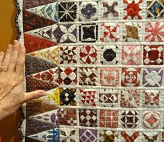 """miniature Dear Jane quilt, Nantes (France), April 2013.  Posted at La Boite de Biscotte.  Note the size of the blocks compared with her hand... each block appears to be about 2"""" square"""
