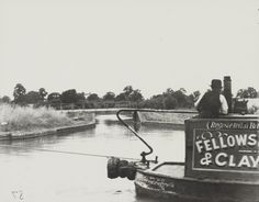 Fellows, Morton & Clayton Limited motor at Norton Junction on the Grand Union Canal Description Black and white photograph showing the stern and part of the cabin of the boat, there is a boatman stood by the cabin. There is a bridge in the distance. Birmingham Canal, Old Boats, Canal Boat, Narrowboat, Old Pictures, Canoe, 1930s, Kayaking, Distance