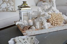 Photo: Friday DIY! Create a coastal vignette in just a few easy steps:  1. Fill a tray with sand (hint: if you don't live near the ocean use our sand vase filler!) 2. Place seaside objects such as faux coral and seashells on sand as desired. 3. Add in a lantern and candles for a little extra ambience.