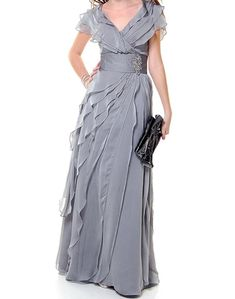 The elegant off the shoulder strap has a waist wrap accented with a beautiful broach. The entire dress is made up big light ruffles all the way to the bottom of this floor length gown. Mother Of The Bride Plus Size, Mother Of The Bride Suits, Gown With Jacket, Plus Size Long Dresses, Floor Length Gown, Dresses Uk, Bride Dresses, Lounge Dresses, Wrap Dresses