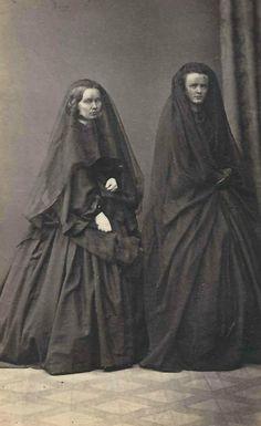 Twee Victoriaanse dames in rouwkleding. Duidelijk zichtbare rouw was toen gebruikelijk. Soms zucht iemand wel eens dat het fijn zou zijn om aan de buitenkant te laten zien dat hij of zij in de rouw is; nu zie je er niets van.