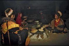 Kalashi women cooking chapatti (bread). The Kalash clan, located in Northern Chitral, Pakistan depend on farming and herding for a livelihood. Chitral, Pakistan.