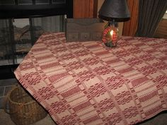 """Our Primitive Cranberry and Tan Woven Coverlet Table Cloth 52x52"""" will offer a unique tablescape for special occasions. Use your favorite old time dishes and add a centerpiece and candles to make for a quiet intimate dinner. https://www.primitivestarquiltshop.com/products/primitive-cranberry-and-tan-woven-coverlet-throw #primitivekitchensanddiningrooms"""