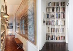 hallways are for books, contemporary design, white bookshelves, large scale art in long hall, wood floors