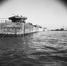 A line of Phoenix caisson units, part of the 'Mulberry' artificial harbour at Arromanches, 12 June 1944., Harrison (Sgt)