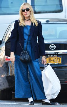 Chloe Sevigny in a chambray jumpsuit, navy blue jacket, black bag, white socks, black loafers, and sunglasses