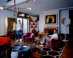"""Britt Moran et Emiliano Salci from #Dimore - Sitting on a Jean Royère """"Ours"""" armchair, coffee table from Gio Ponti, golden wardrobe from Freek Wambacq, light """"Luciferase"""" from Nacho Carbonell"""