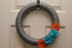 This wreath is and wrapped with grey yarn with orange and turquoise felt flowers. The wreath can be hung with the orange ribbon or without. Yarn Wreaths, Orange And Turquoise, Kids Zone, Felt Flowers, Color Inspiration, Color Schemes, Crafting, College, Bows